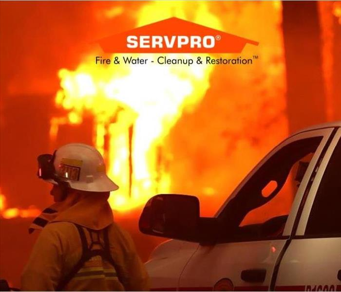 A firefighter with a hat on next to a white truck and fire in the background and the SERVPRO logo at the top center