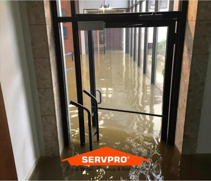 A glass door with flood water filling up the building
