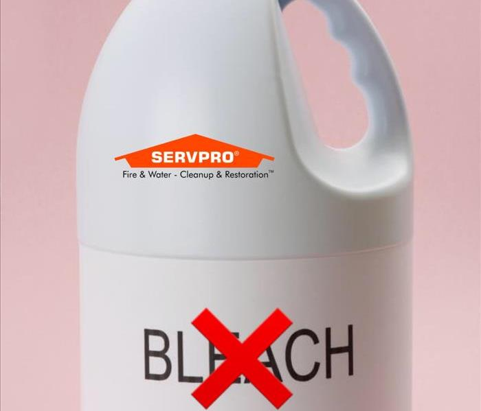 A white bottle with the word bleach on it and a red X through it also with the SERVPRO logo at the top
