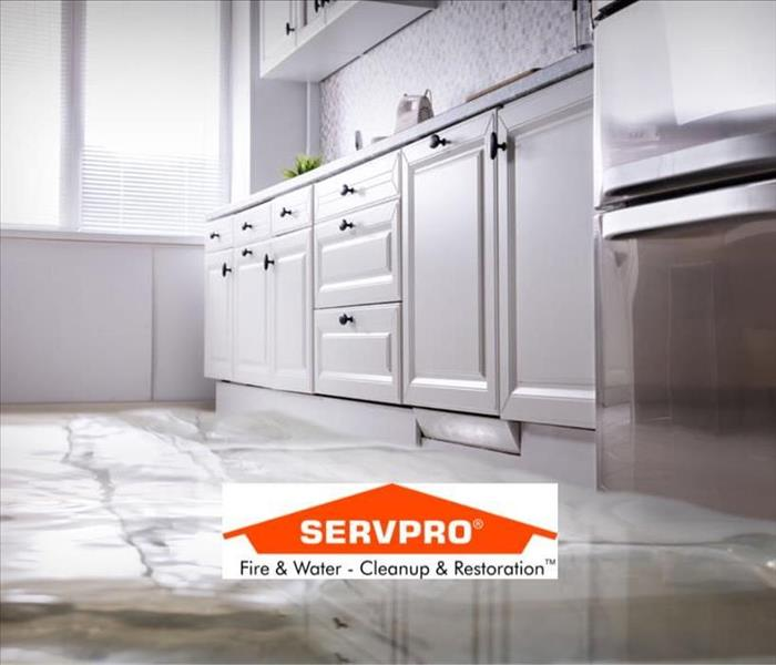 a photo with water on the floor of a kitchen and the SERVPRO logo