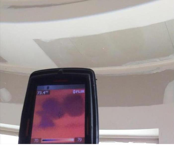 A close up picture of a moisture meter that lights up pink and dark purple when it is facing a white and tan colored ceiling.