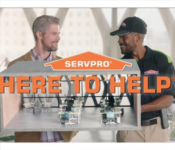 A SERVPRO employee talking to a customer with the here to help words in the middle of the picture